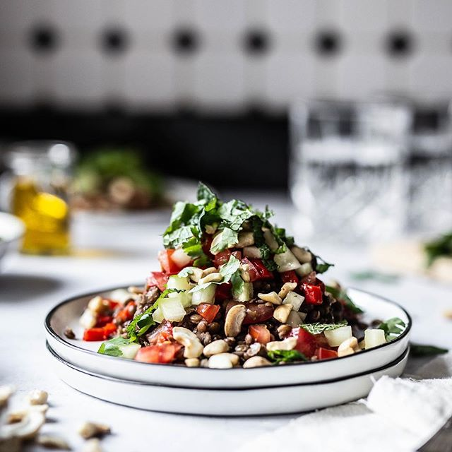 (Werbung/Verlinkung) Linsen und Kichererbsen sind zwei unserer absoluten Favoriten 😊. Für @koro_de haben wir zwei tolle Rezepte mit diesen vielfältig einsetzbaren Sattmachern vorbereitet. Heute starten wir mit Linsen, die wir zusammen mit ofengerösteten Paprika, Tomaten, Gurken und der Gewürzmischung Ras el Hanout in einen wunderbaren lauwarmen Salat verwandelt haben. Und für den Extra Crunch gab es noch etwas Cashew-Bruch als Topping oben drauf. 🥗🌶🥒🍅⠀ ⠀ 👉 Foodstyling: frische Kräuter für das gewisse Etwas⠀ ⠀ Um unseren Linsensalat auf dem Foto möglichst appetitlich aussehen zu lassen, haben wir jede einzelne Zutat des Salates ganz bewusst platziert. Damit auch wirklich jedes Stück Gurke und Tomate seinen richtigen Platz findet, kam hier auch wieder unsere Pinzette zum Einsatz. ⠀ ⠀ Da insbesondere Kräuter wirklich schnell verwelken und dann nicht mehr schön aussehen, platzieren wir Kräuter erst ganz am Ende. Außerdem arbeiten wir am liebsten mit Kräutertöpfen für maximale Frische. Alternativ wickeln wir abgeschnittene Kräuter bis zur Verwendung schonmal in ein feuchtes Küchentuch ein, denn auch so bleiben sie länger frisch. 😊⠀ .⠀ .⠀ .⠀ 📷 Canon EOS 6D / 50mm / ISO 250 / f/2,0 / 1/100⠀ .⠀ .⠀ .⠀ .⠀ .⠀ .⠀ #herbstrezept #herbstküche #linsensuppe⠀ #korolicious #gesunderezepte #gesundundlecker #gesundessen #gesundeernährung #zuckerfrei #ohnezucker #ballaststoffe #gesundeküche #organicfood #linsen #vegandeutschland #vegangermany #raselhanout #vegetarisch #orientalisch #stilllifegallery #cookmagazine #foodstylingandphotography #foodinspirations #foodstyleguide #vscfood #persianfood #thrivemags #essenundtrinken #foodblogliebe #rezeptideen⠀ @Foodandwine @lecker_magazin @brigittemagazin @essenundtrinken_magazin @livingathome_magazin ⠀