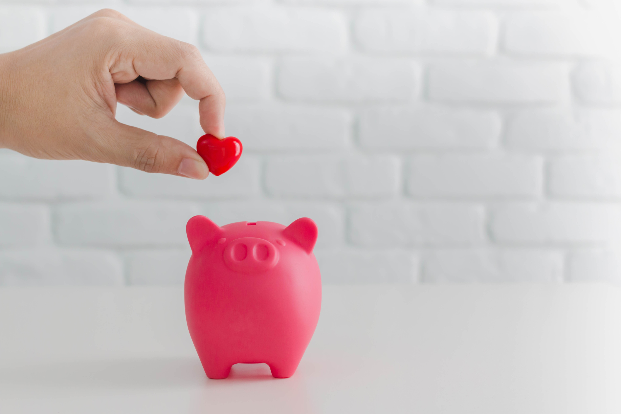 Man's-hand-putting-red-heart-in-to-piggy-bank-metaphor-saving-love-for-lover-or-family-in-every-day.Concept-of-happy-relationship.-911910830_2124x1416.jpeg