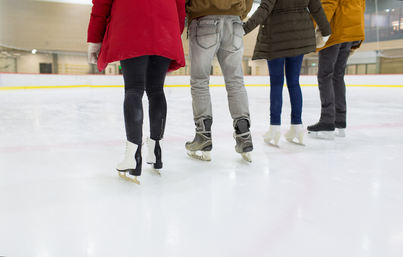 close-up-of-happy-friends-skating-on-ice-rink-502258496_1283x820.jpeg