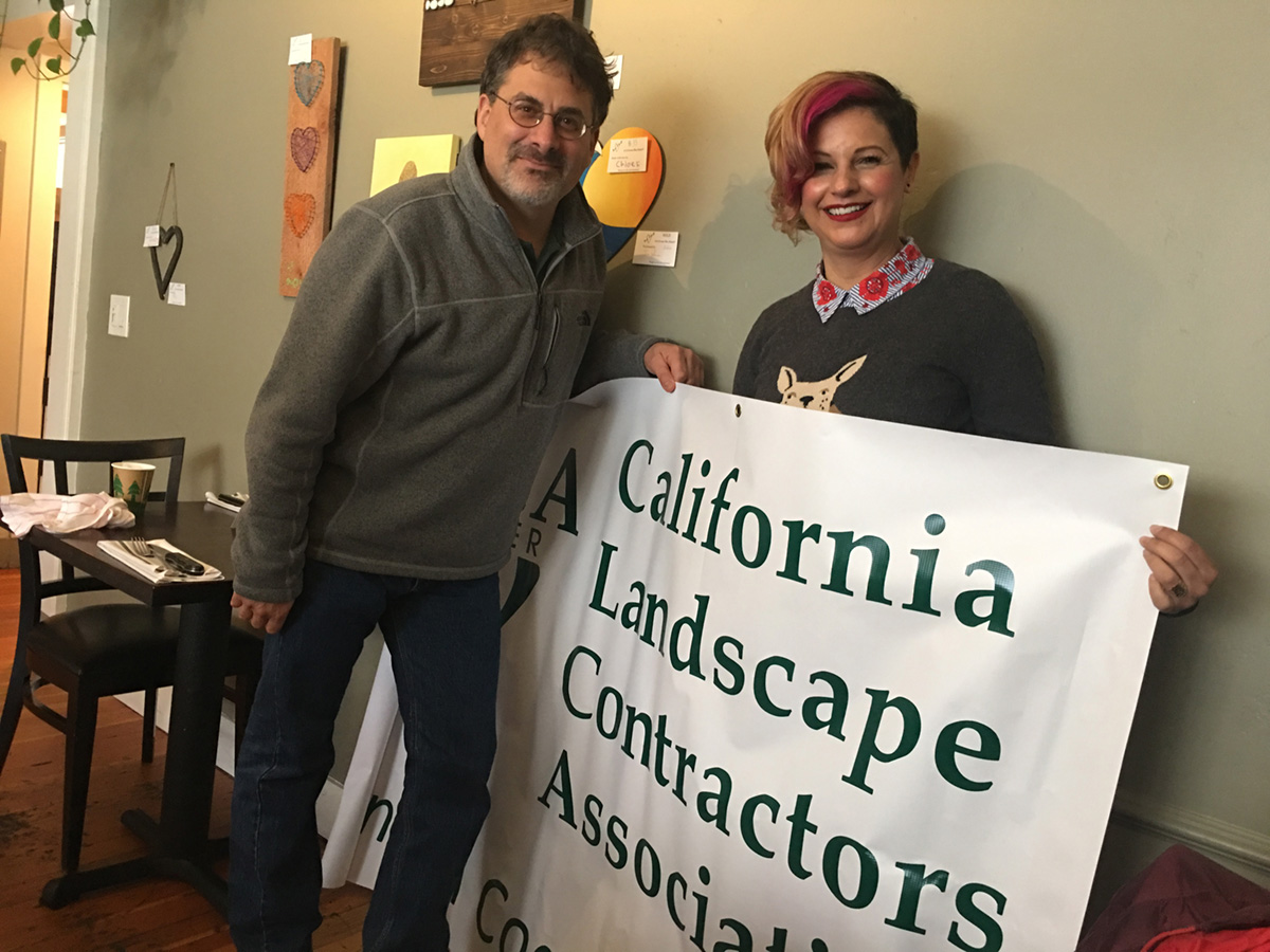 Andrew Tuckman hands the CLCA Central Coast banner over to Katia Velasquez, the new Events Coordinator.