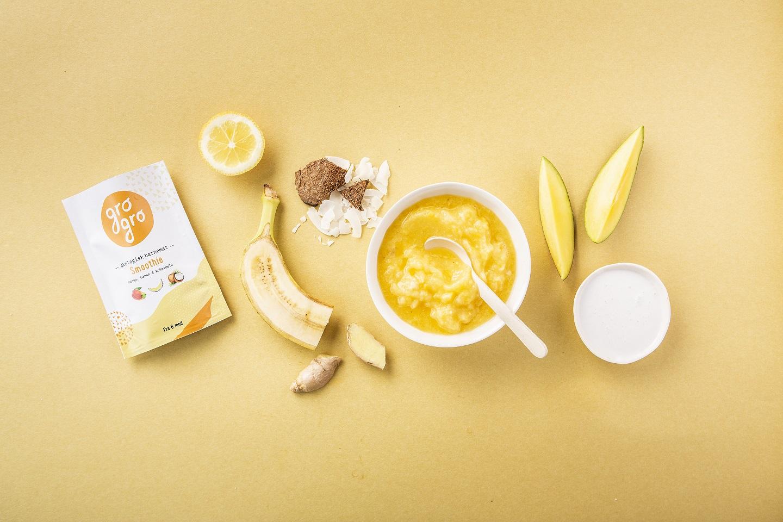 Mango- og banansmoothie med ingefær og sitron - Anbefalt fra 6 måneder. 120 g/pakke.Ingredienser: Mango 39%*, Banan 39%*, , kokosmelk 15%, sitronsaft fra råsaft 5%*,tørket ingefær 2%*,*Økologiske ingredienser.Næringsinnhold per 100 g:126 kcal/527 kJ, Fett 4,43g (hvorav mettede fettsyrer 0.11g Flerumettede fettsyrer 0.11g Enumettede fettsyrer 0.06g, Karbohydrat 19,0g, Kostfiber 1,89g, Protein 1.51g, Salt 0mg