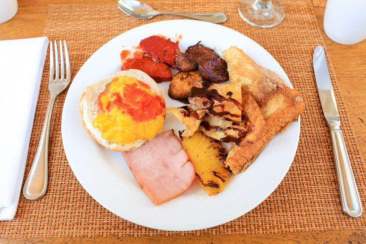 A Dominican breakfast, including eggs and salsa, sausage, fried plantains, sweet tortillas, cinnamon french toast, grilled pineapple and ham. The absence of vegetables was a common theme.