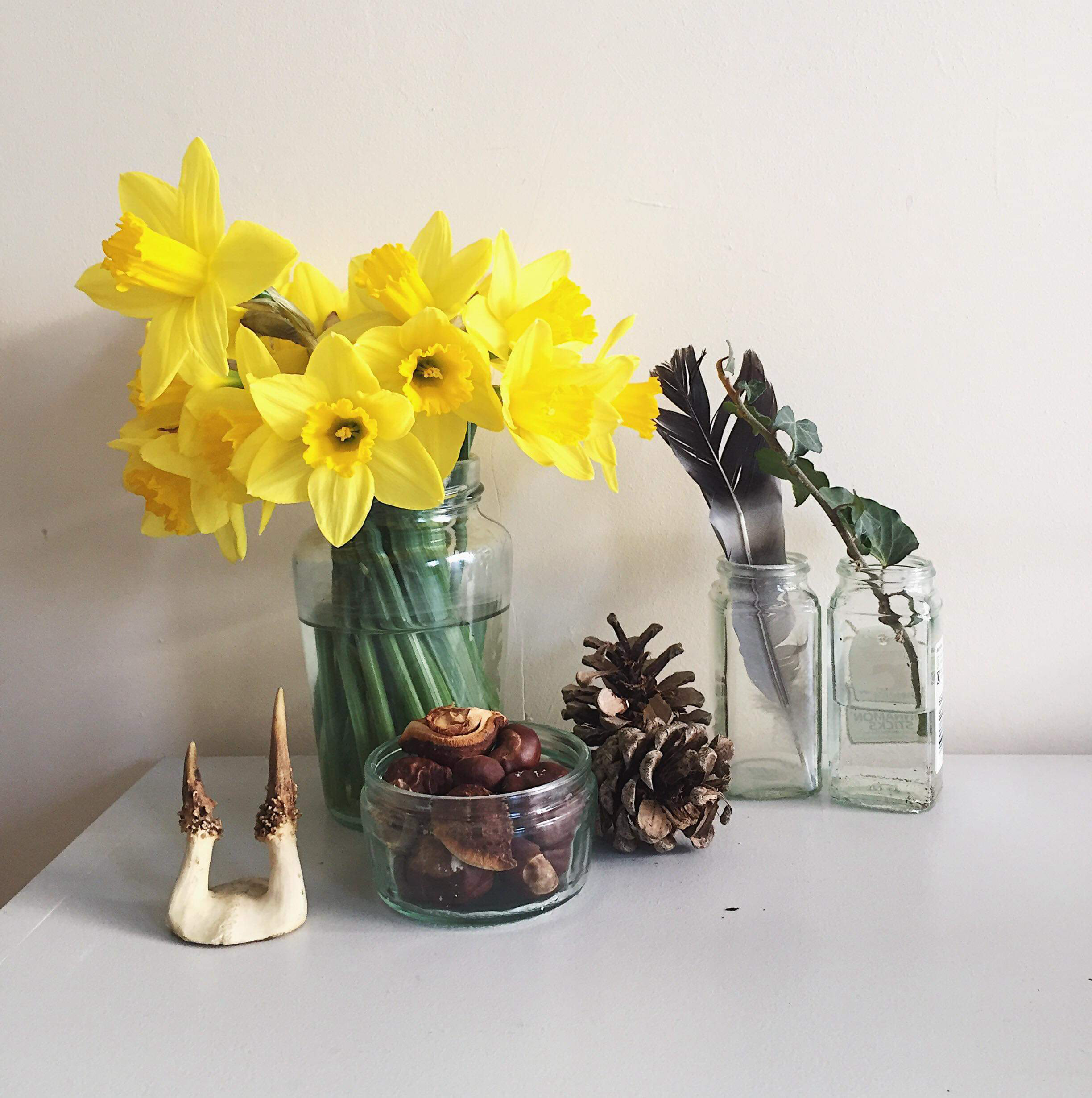 A few natural treasures on a side in the living room; some found conkers, pine cones, a bunch of flowers and a much loved feather that was carried the whole way home.