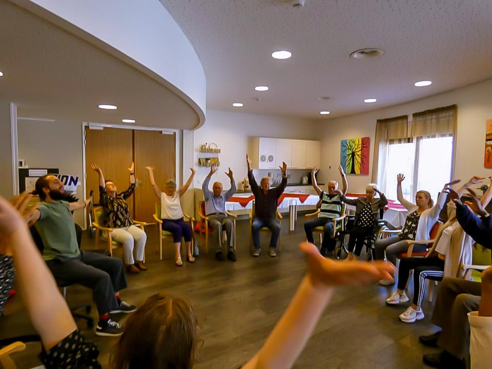 Foto beschrijving: Je ziet mensen in een cirkel zitten met hun armen om hoog, met een glimlach op hun gezicht, een onderdeel van de dansles.  Foto van: Ontmoetingscentrum Lyvore