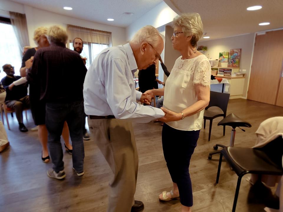 Beschrijving foto: Twee dansparen op de vloer hand in hand. Op de voorgrond een man (65+) met zijn vrouw. Op de achtergrond zie je de docent die blij kijkt naar wat er gebeurt en zie je een man die geniet van de muziek.  Foto van: Ontmoetingscentrum Lyvore
