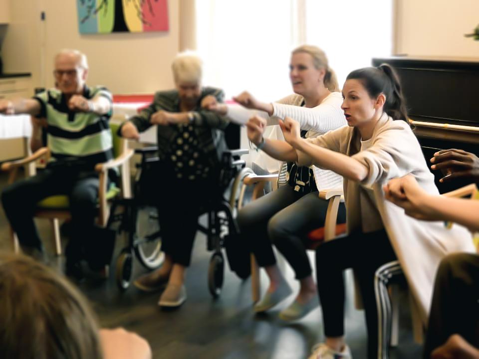 Foto beschrijving: 4 Mensen zitten op een stoel naast elkaar, hun armen rijken naar voren en hun handen zijn tot een vuist gebald. De dansleraar, die de beweging met empathie uitvoert, is scherp in beeld weergegeven.  Foto van: Ontmoetingscentrum Lyvore
