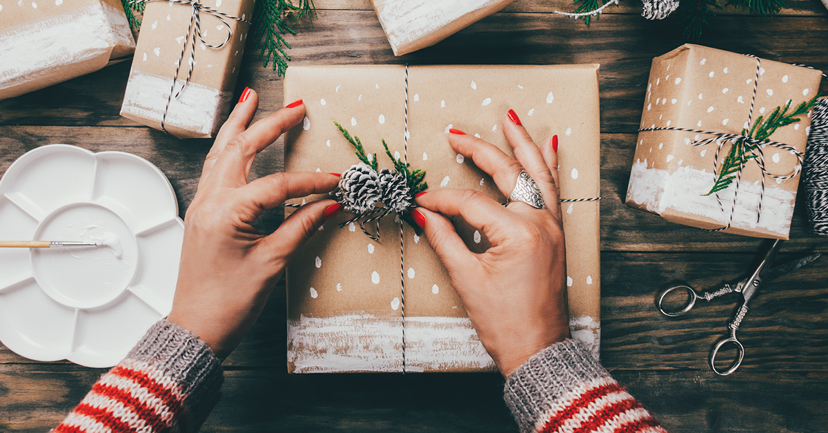 hands placing pine cone decoration on gift