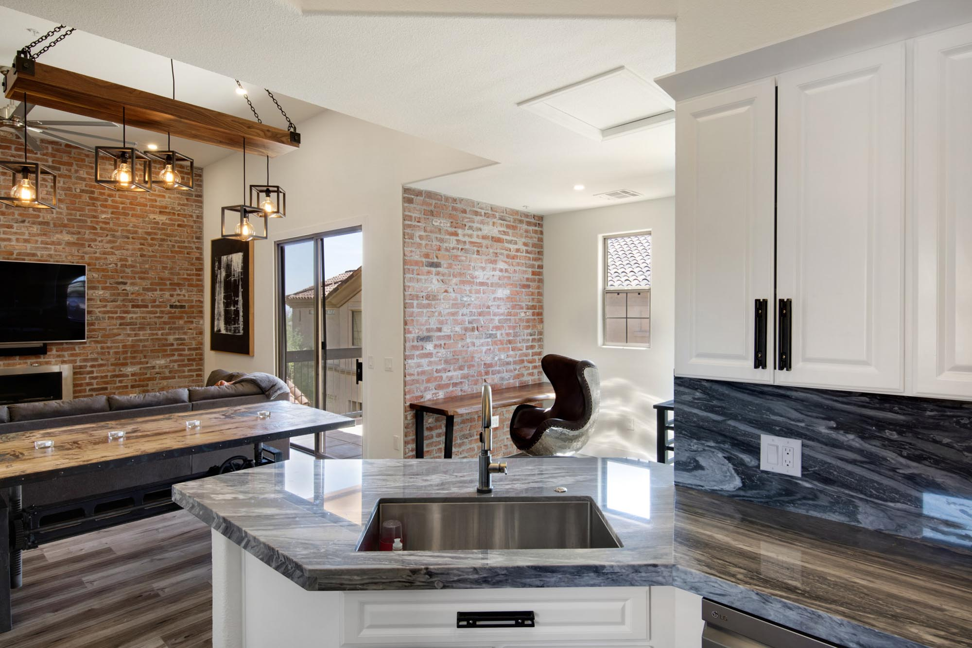 Living room with stylish hanging lights and granite countertop sink