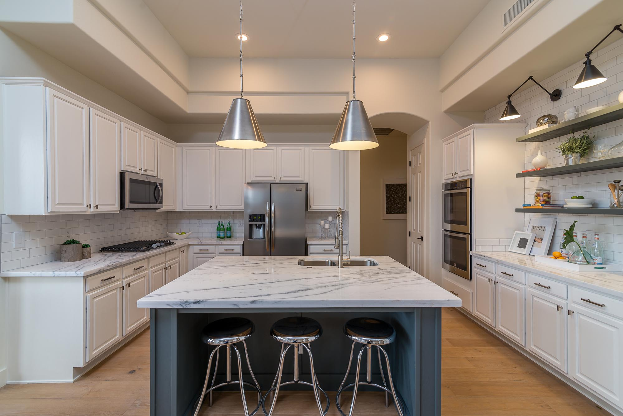 Kitchen with black and white countertops and three bar stools