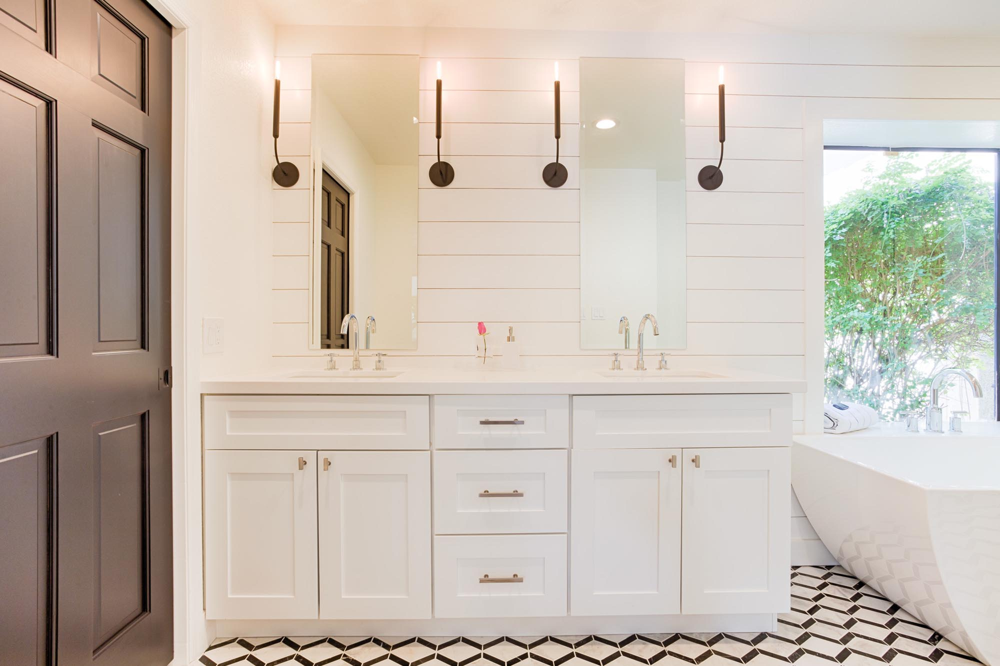 Bathroom with white countertops sink and cabinets with mirrors
