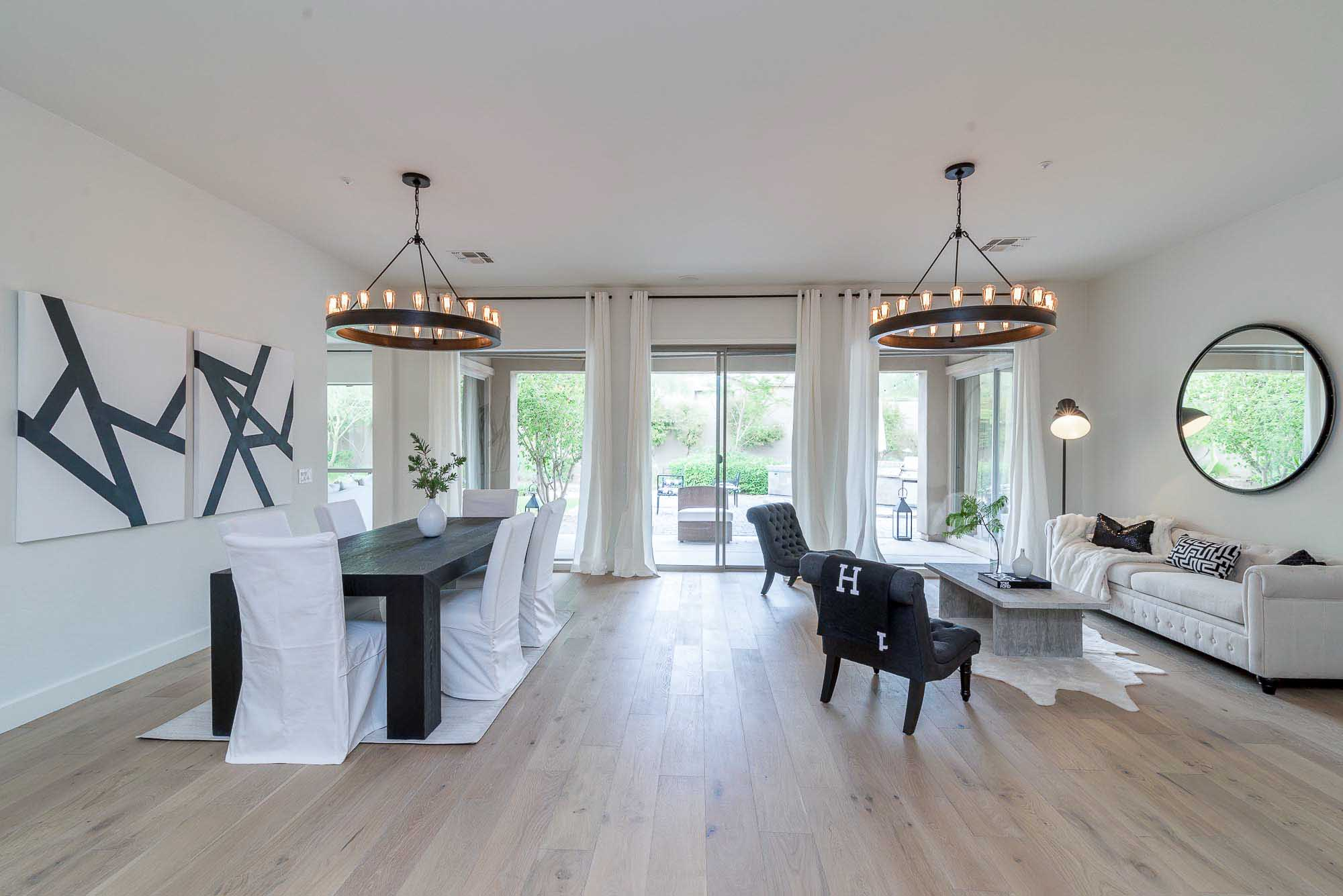 Modern living room with dining table for six and chandeliers
