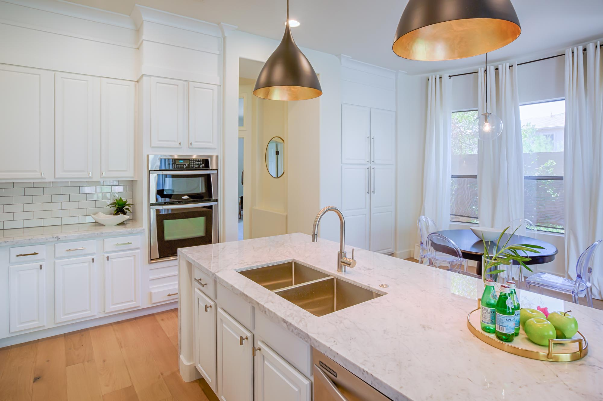 Kitchen with white cabinets and a tray of apples and drinks on island