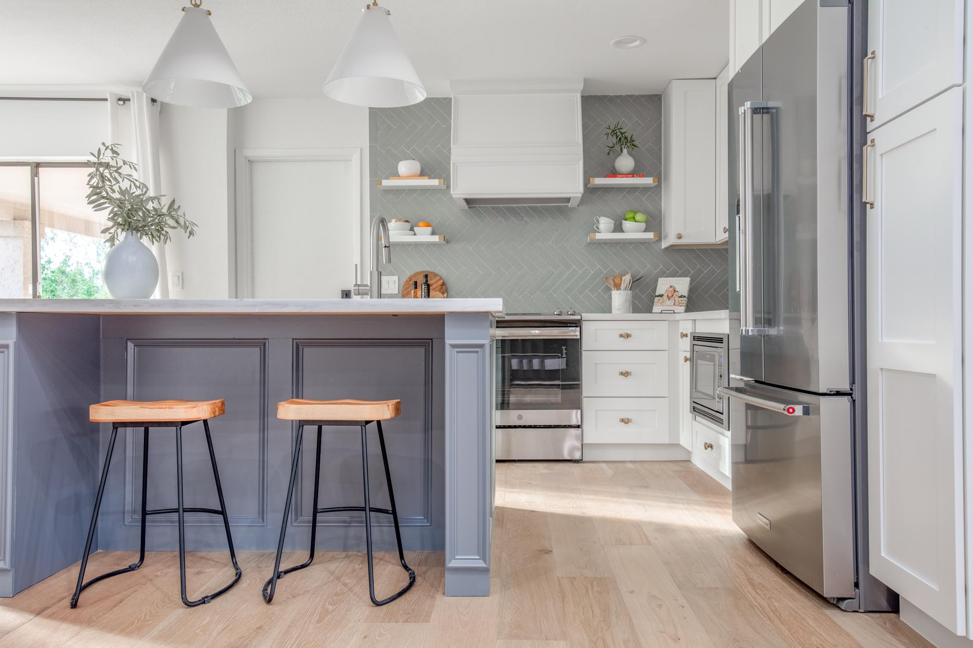Kitchen with two bar stool and vase with plant on center island