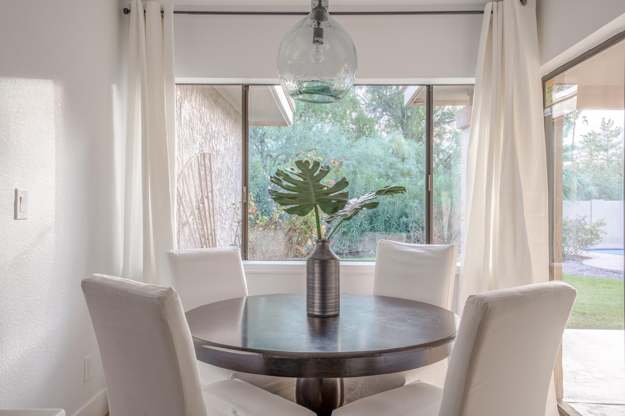 Wooden round table for four with white chairs