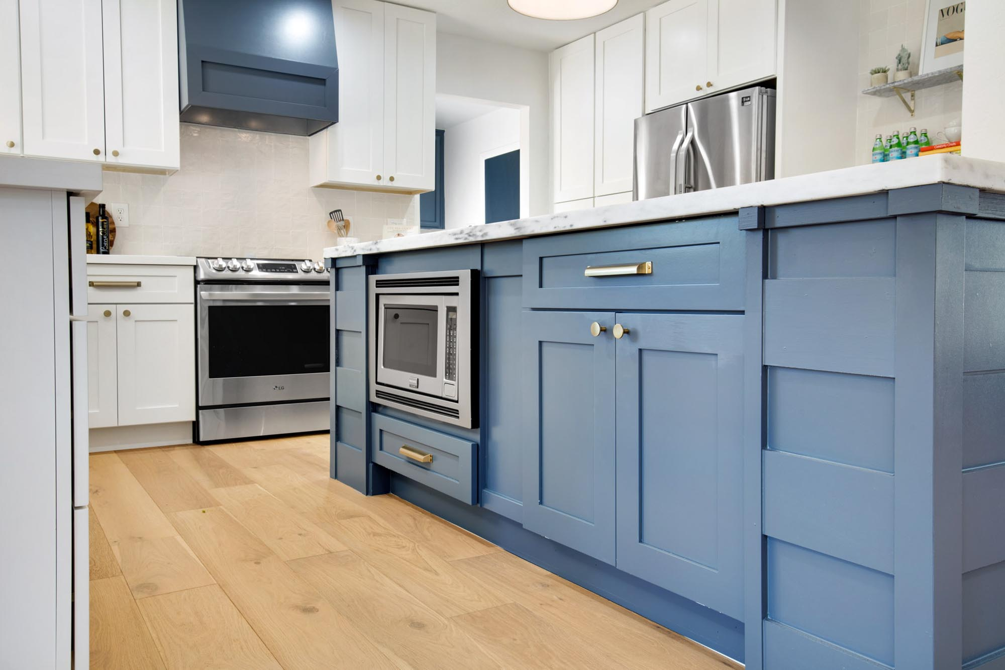 Kitchen with blue painted island cabinet and white countertops