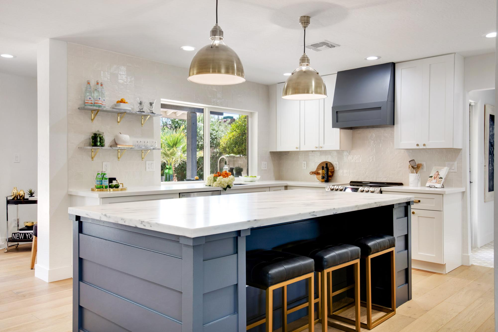 Kitchen with granite countertops island and three black cushioned stools
