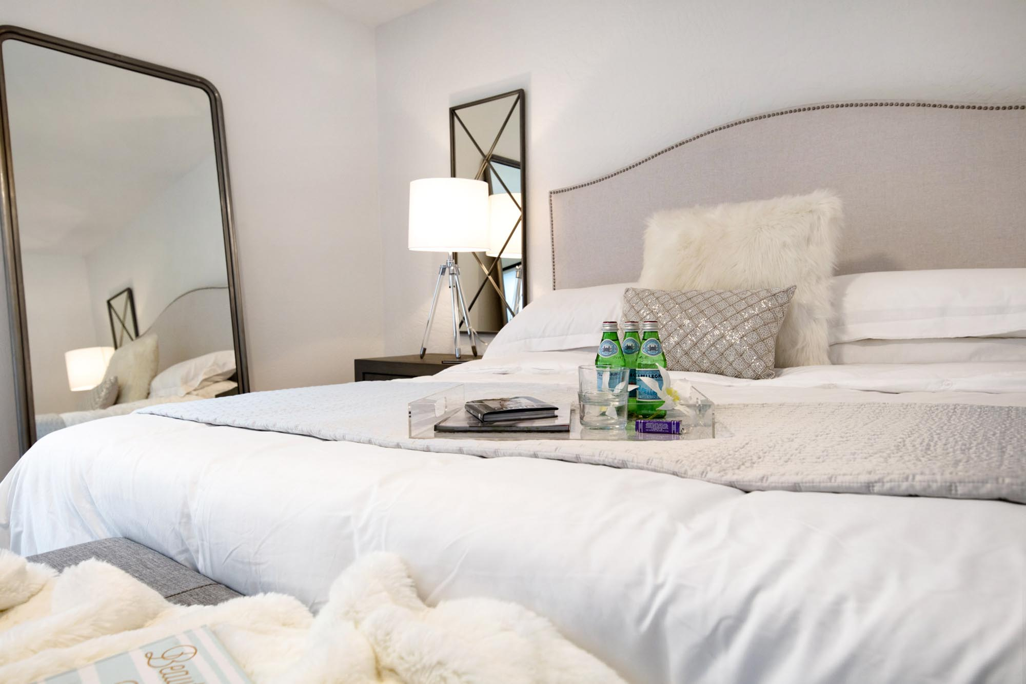 Bedroom with double sized bed and drinks on white bedding