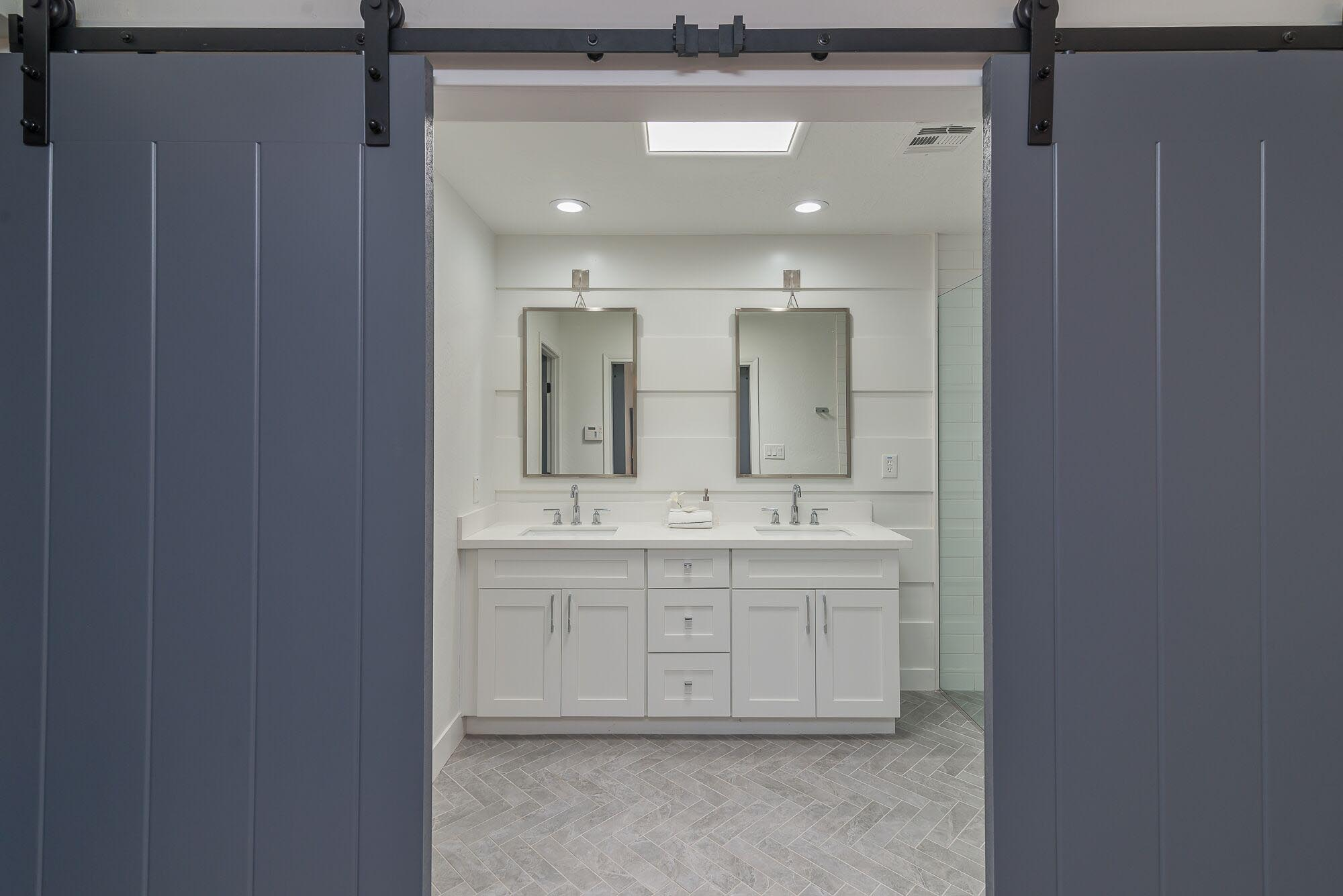 Washroom with white sink cabinets and mirrors