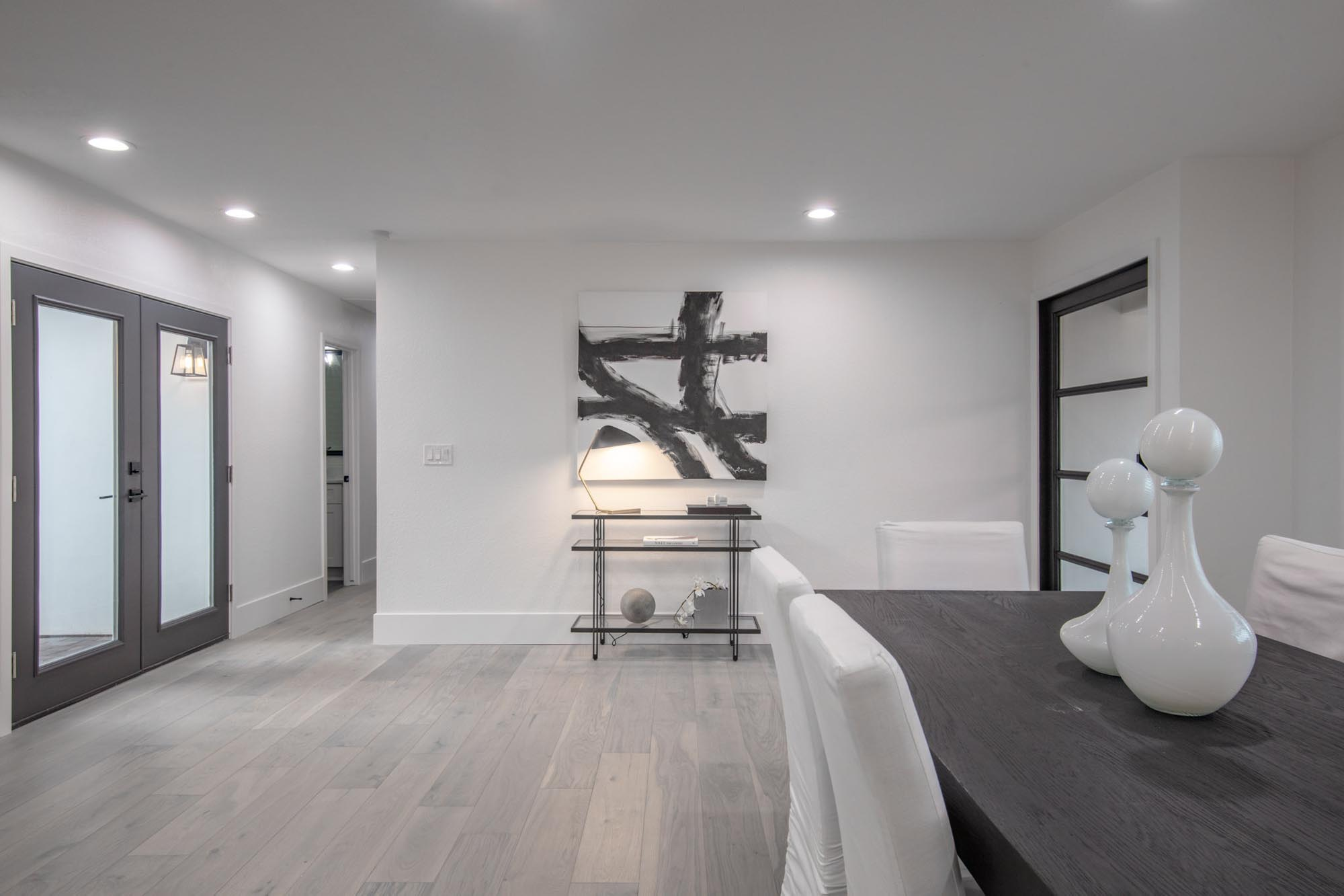 White painted room with abstract painting and shelves