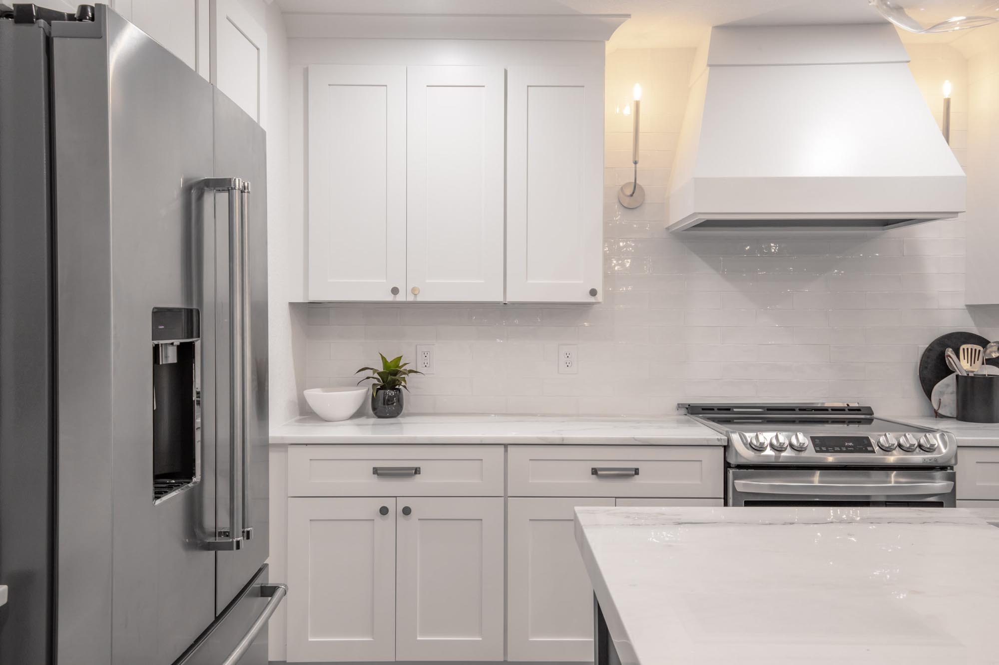 Kitchen with candle like lights and plant on white countertops