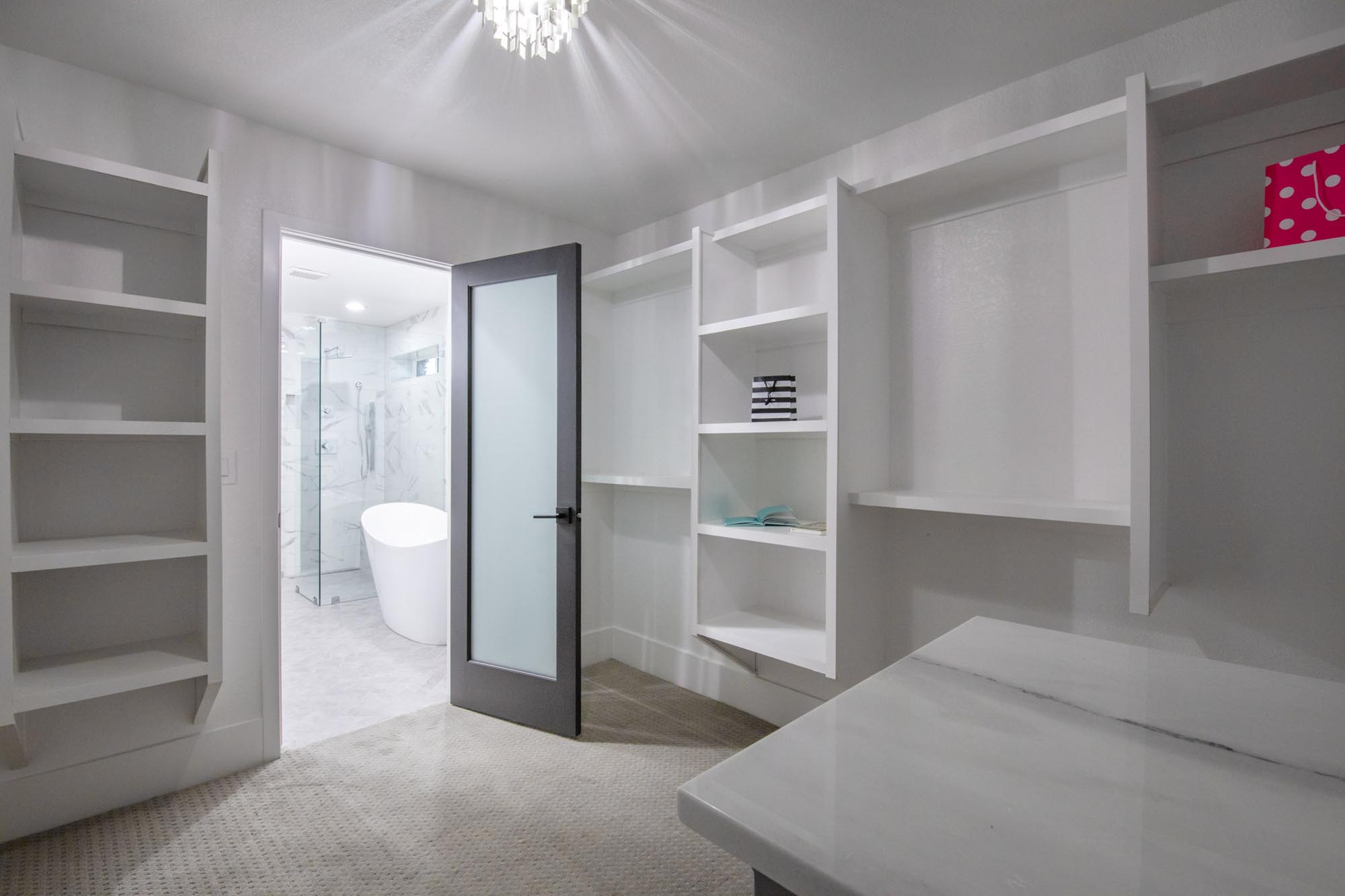 Room with white shelves and entryway to bathroom