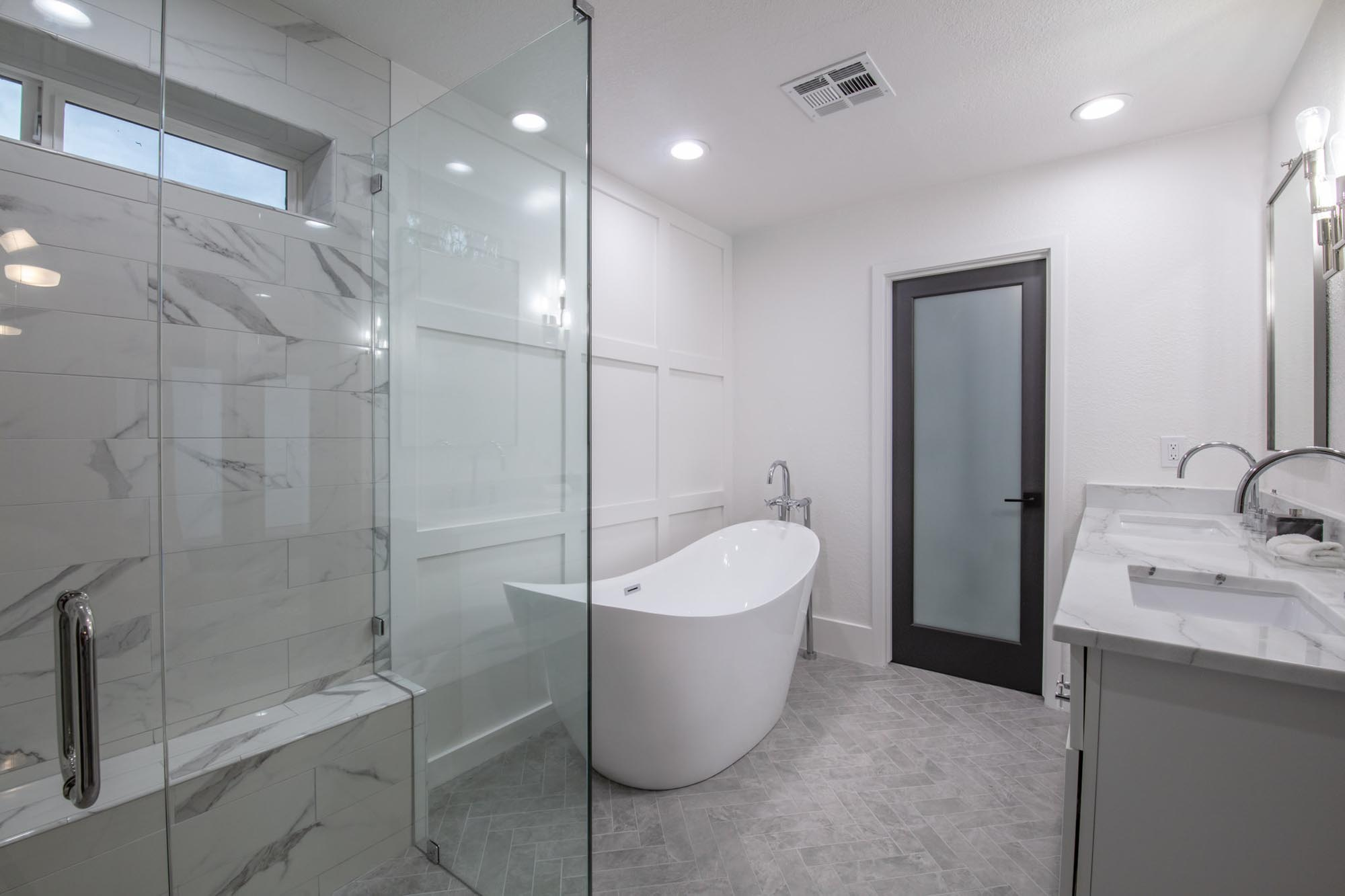 Bathroom with glass shower room and white bathtub