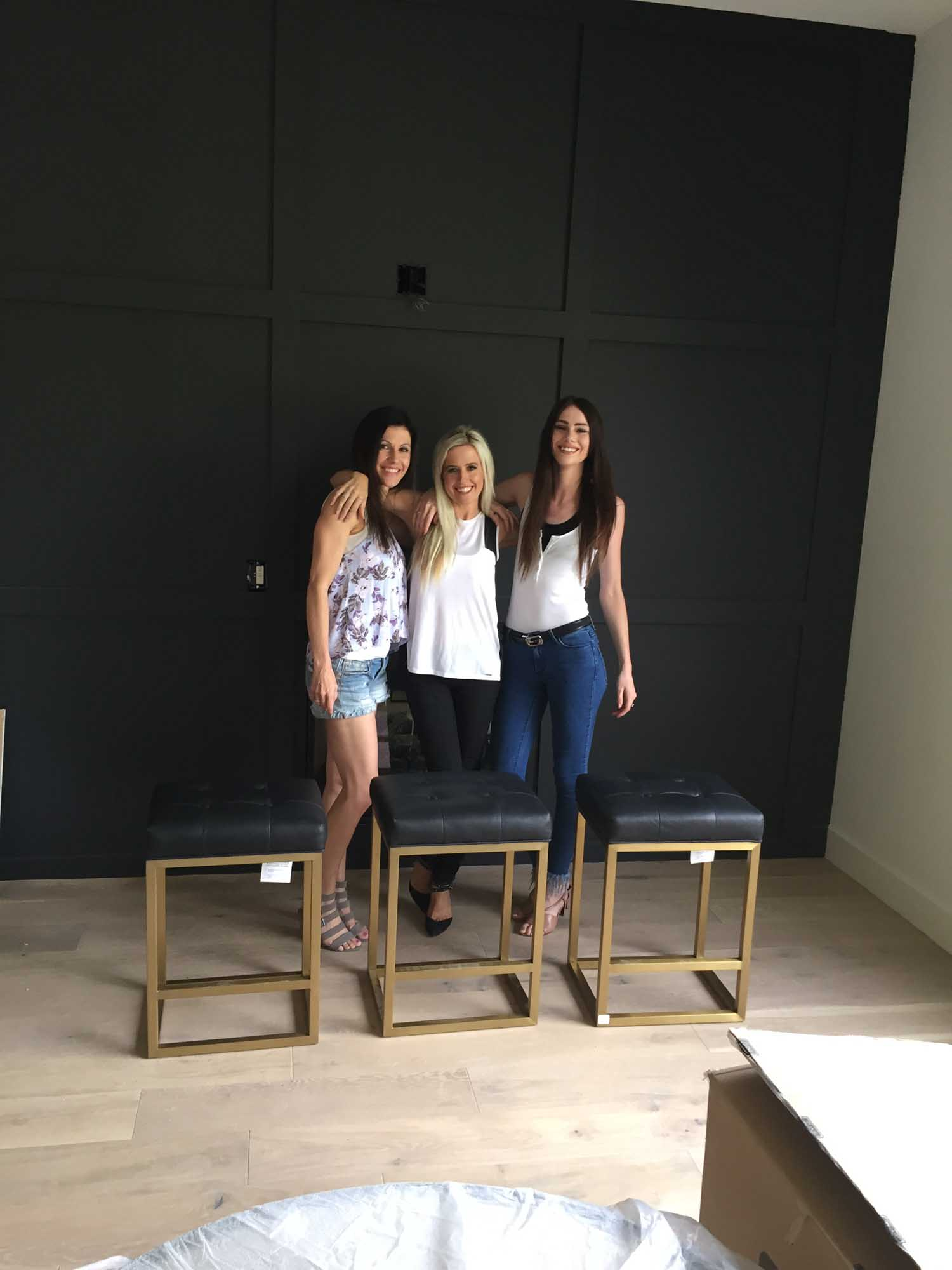 Three women standing with black painted wall