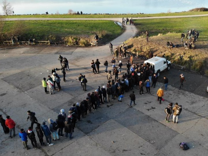 Homeless refugees queue for hot food which is brought daily by Refugee Community Kitchen, Calais