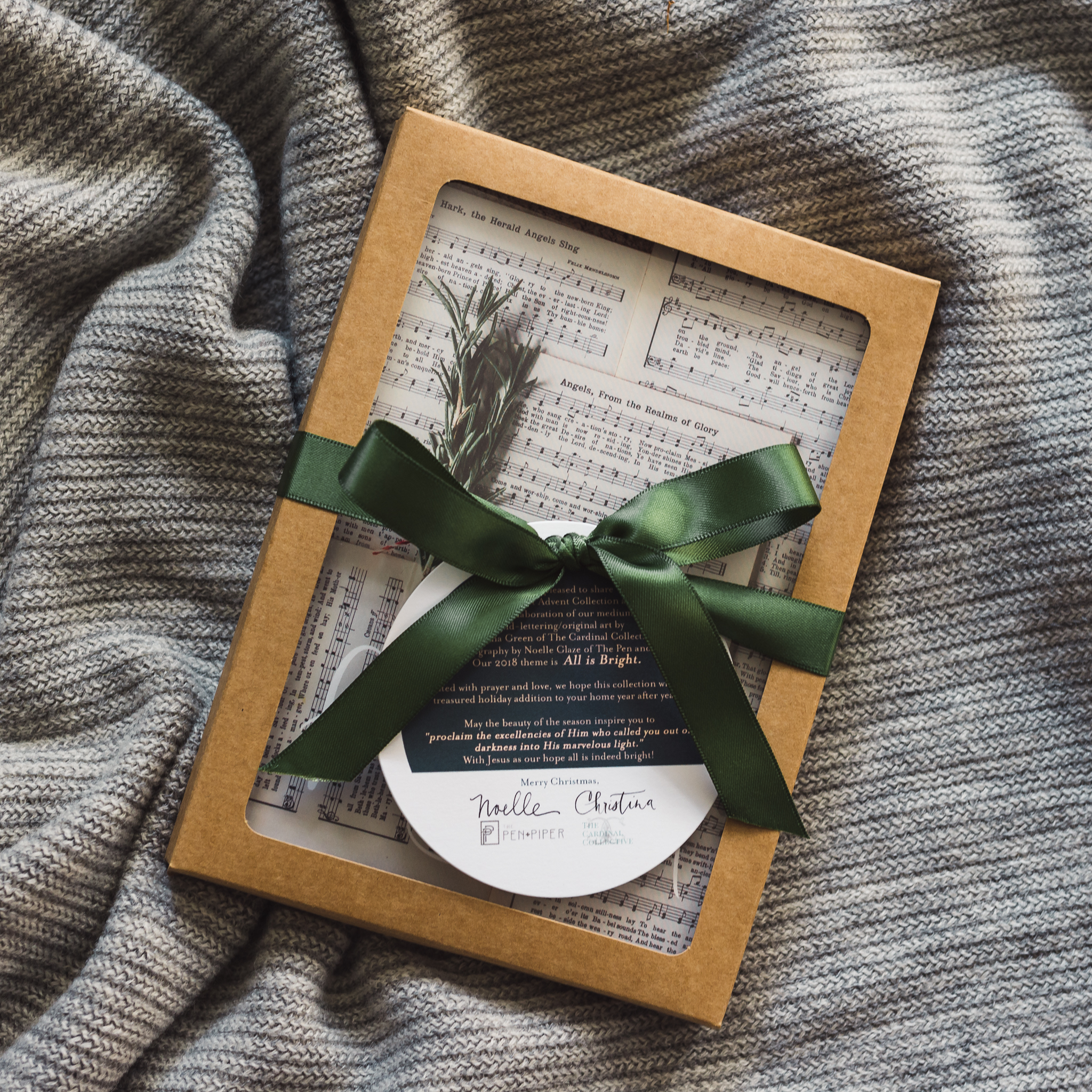 """Beautifully Packaged - The """"All is Bright"""" Collection will arrive prepacked in a Kraft paper box with a transparent window, tied with a color-coordinating ribbon with a hangtag which introduces the artists and gives an overview of the series."""