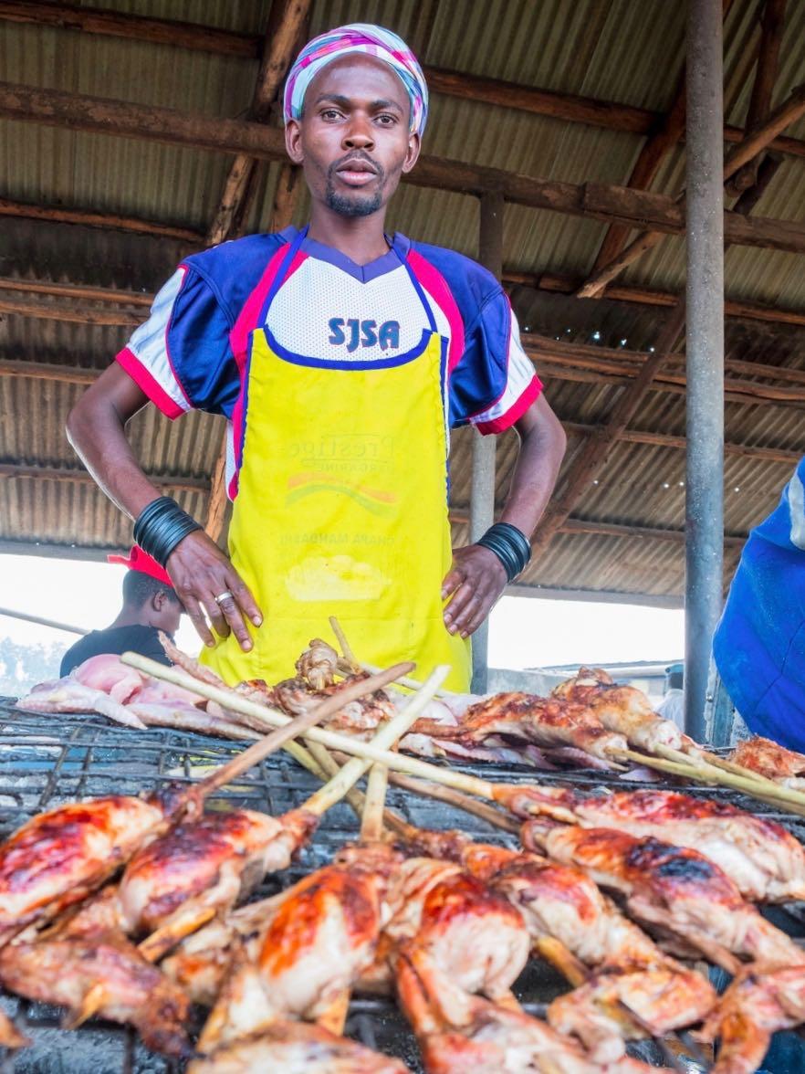 Man selling chicken at roadside foodstop, Entebbe