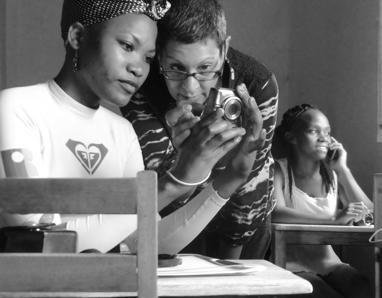 Amina instructing student on camera settings, Cameras for Girls Uganda