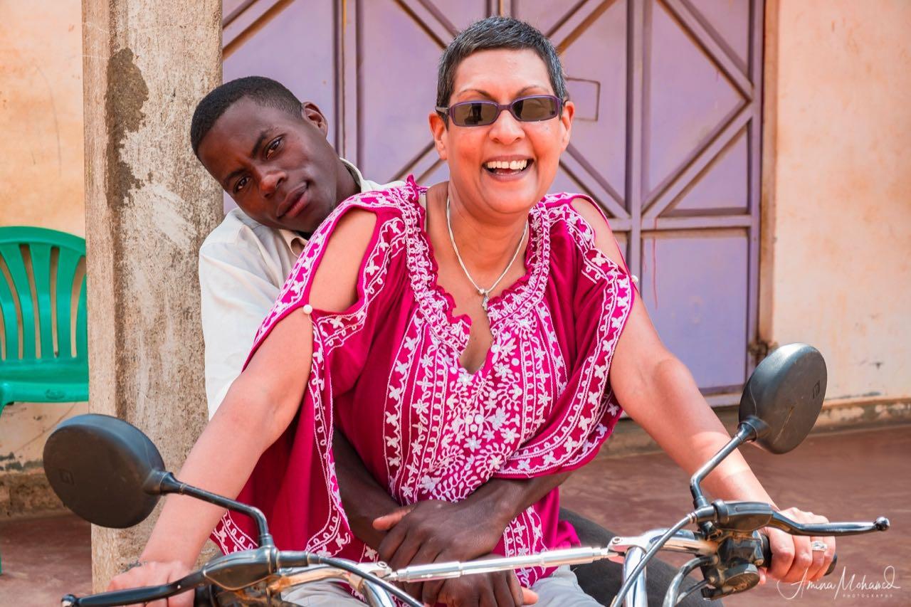 Amina driving a boda boda, while the driver sits behind, Bombo Town, Uganda