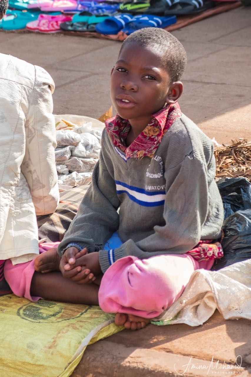 Little girl sitting on a corner selling fruits and vegetables with her mother, Kampala