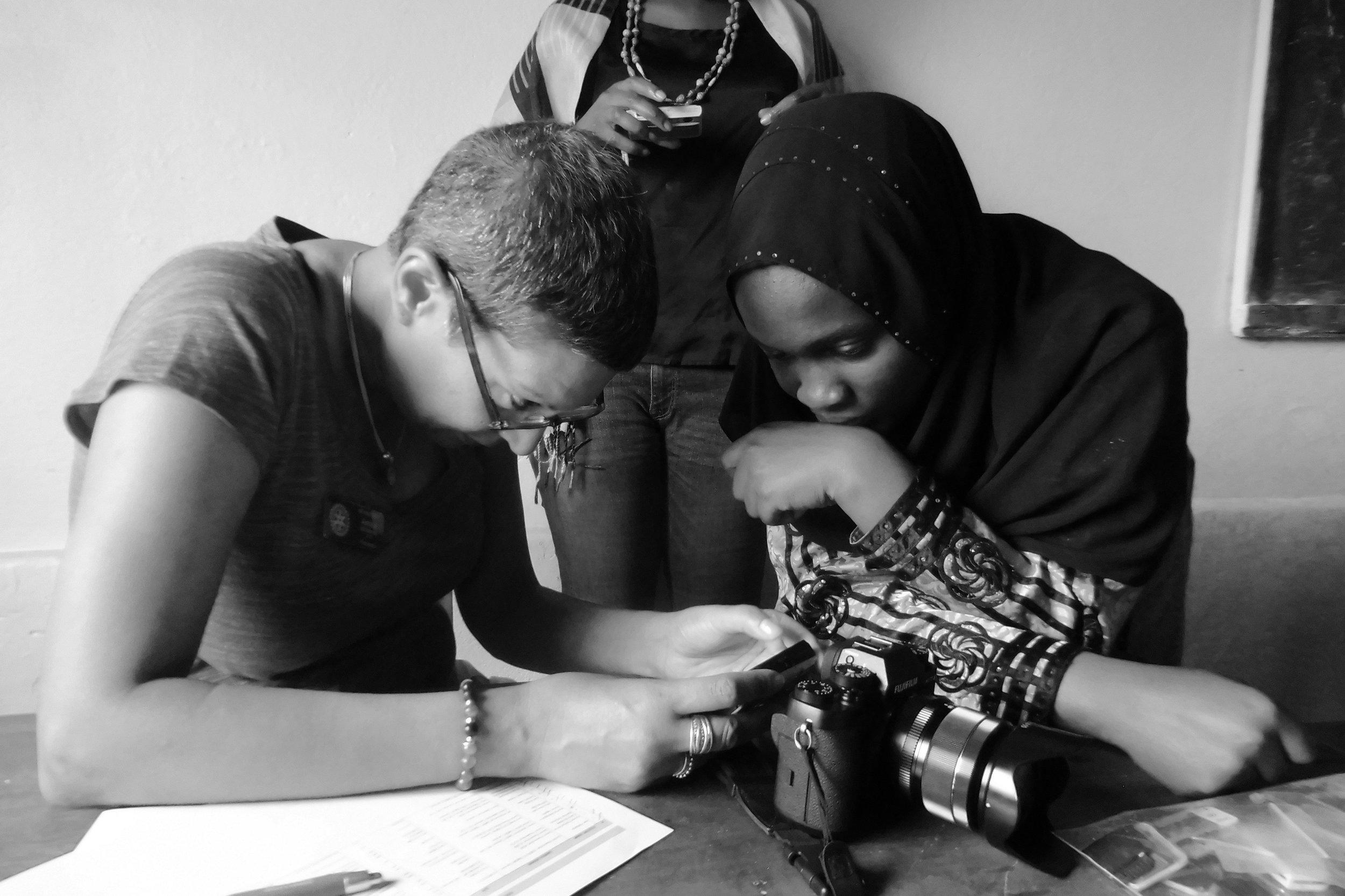 Amina showing Hafitha how to operate her camera, Cameras for Girls Uganda