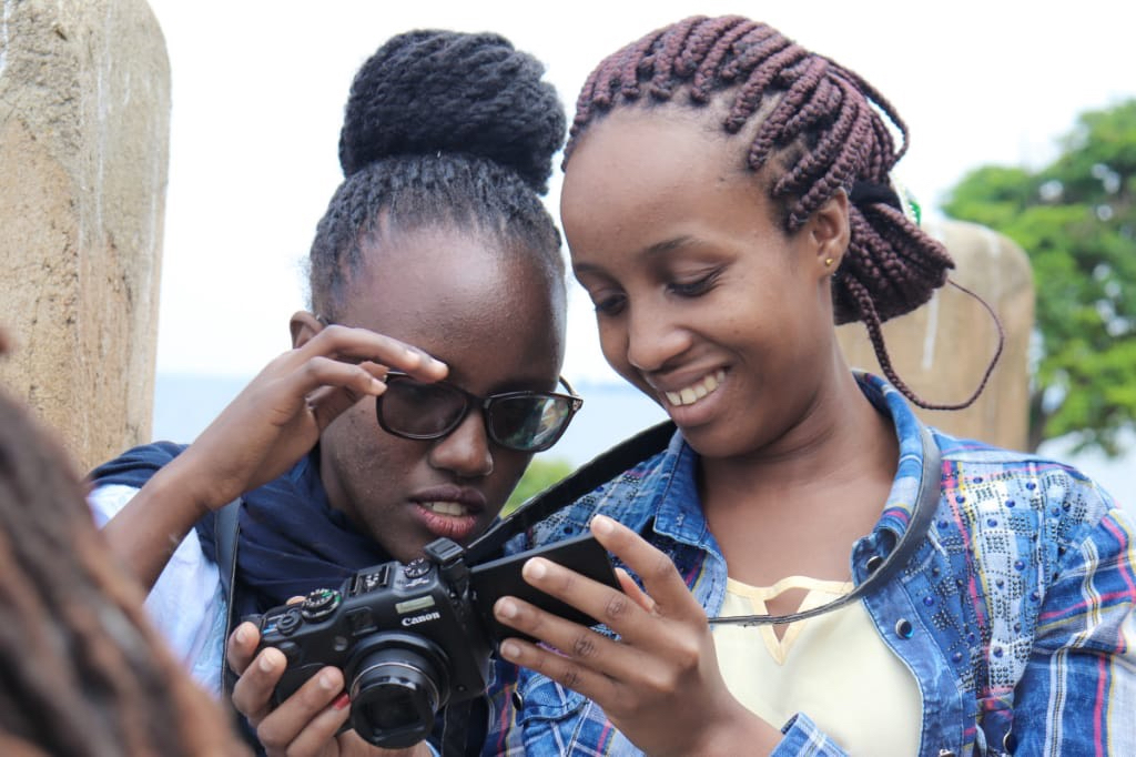 Prisca and Diana looking over an image they took at the Youth Arts Movement Camp