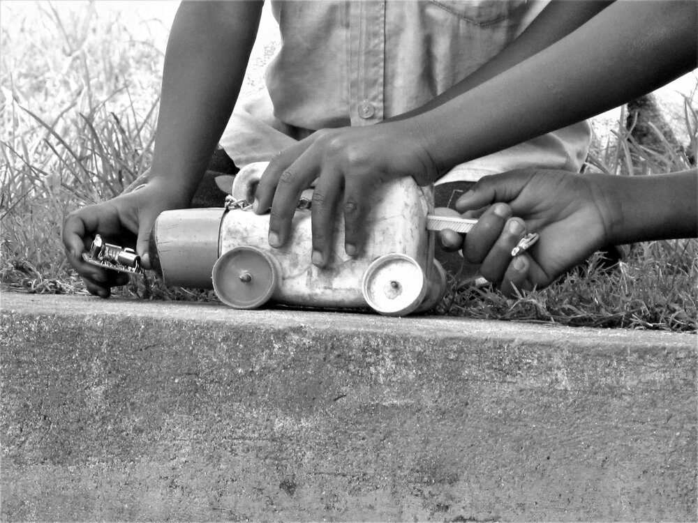 Taken during quarantine of local children playing with a toy made from found objects