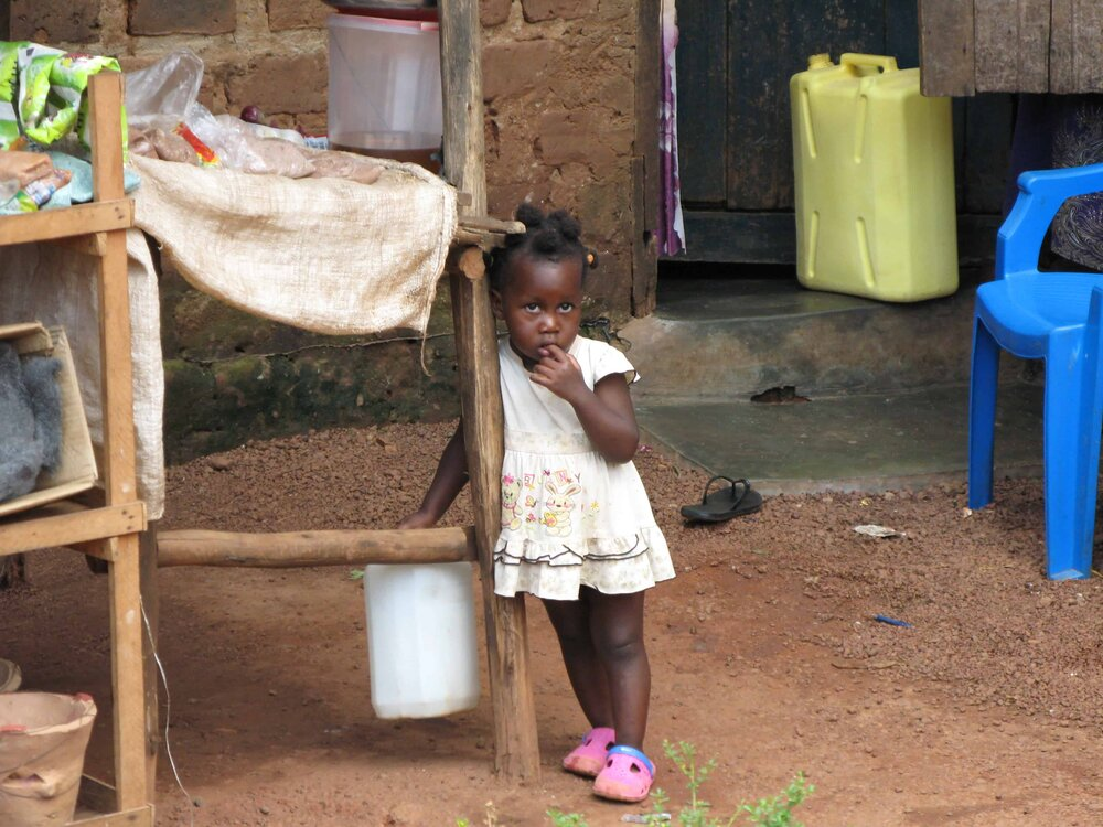 Photo credit Samantha Byakatuga - little girl standing outside of her home in Kampala, Uganda