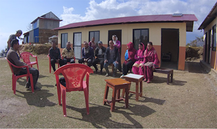 Deurali Community Committee meeting with Baseri Clinic in background.