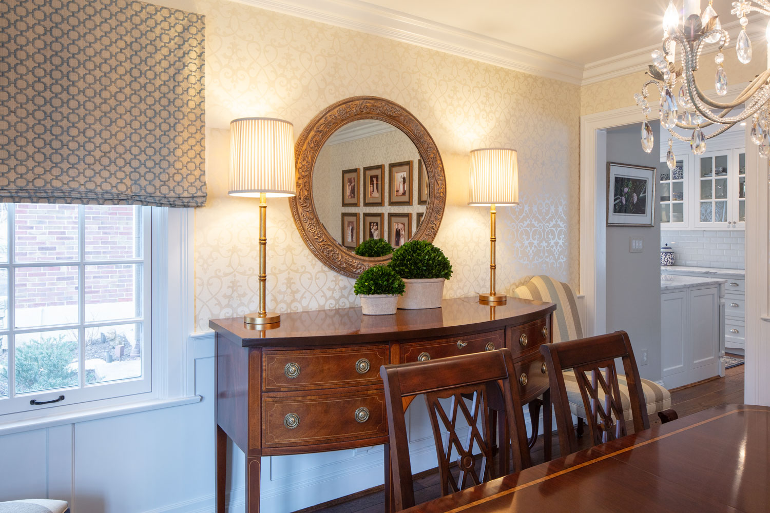 Dining room with wooden table, chairs, table lamp and mirror on the wall