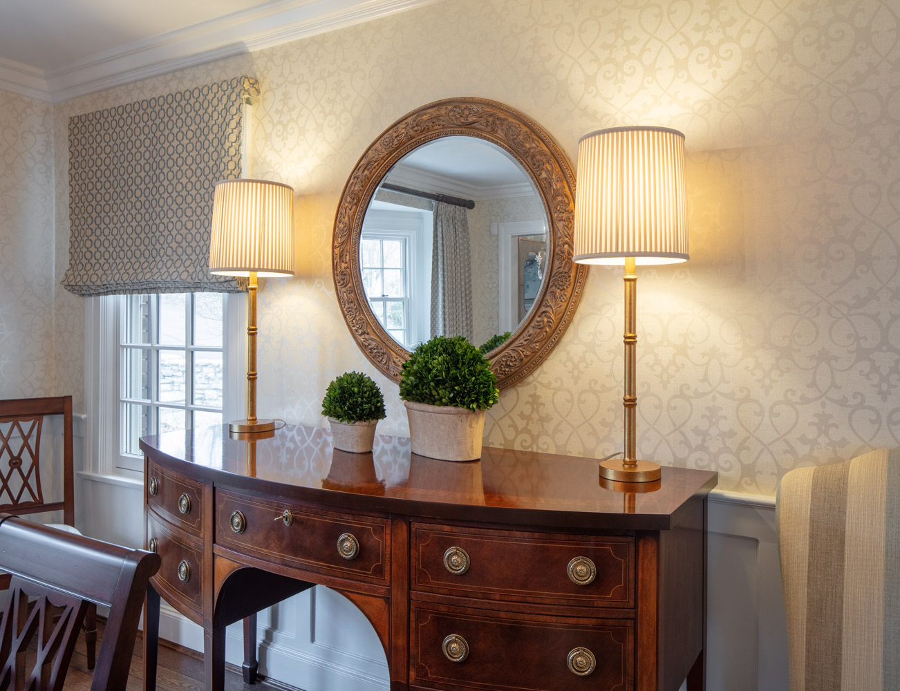 Wooden cabinet, table lamp and a round mirror on the wall