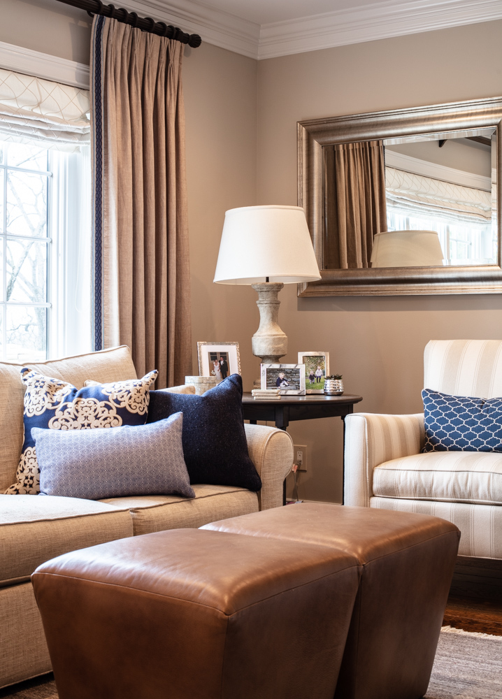 Sofa with set of pillows, a mirror and a wooden round table on the side