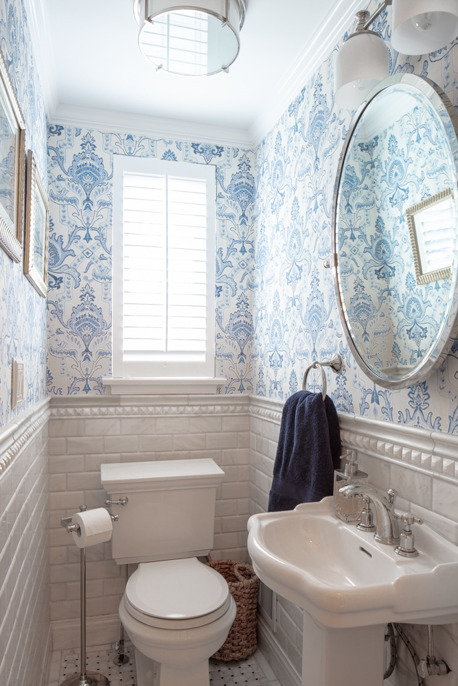 Small toilet room with lavatory, round wall mirror and wall frames