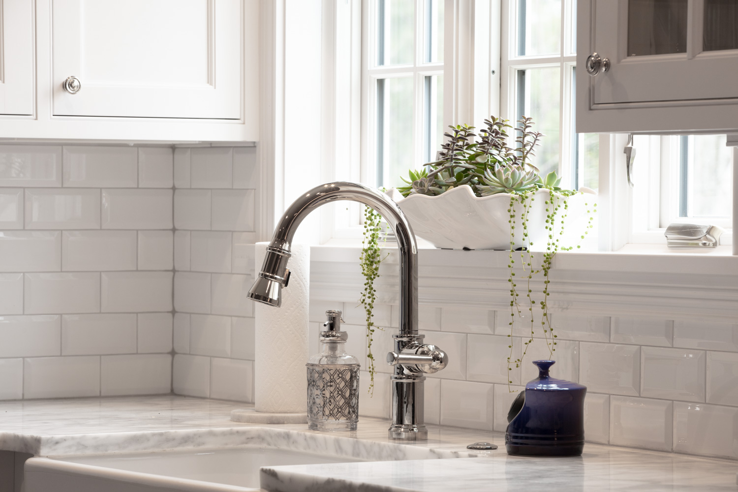 Stainless faucet and a plant on a window sill