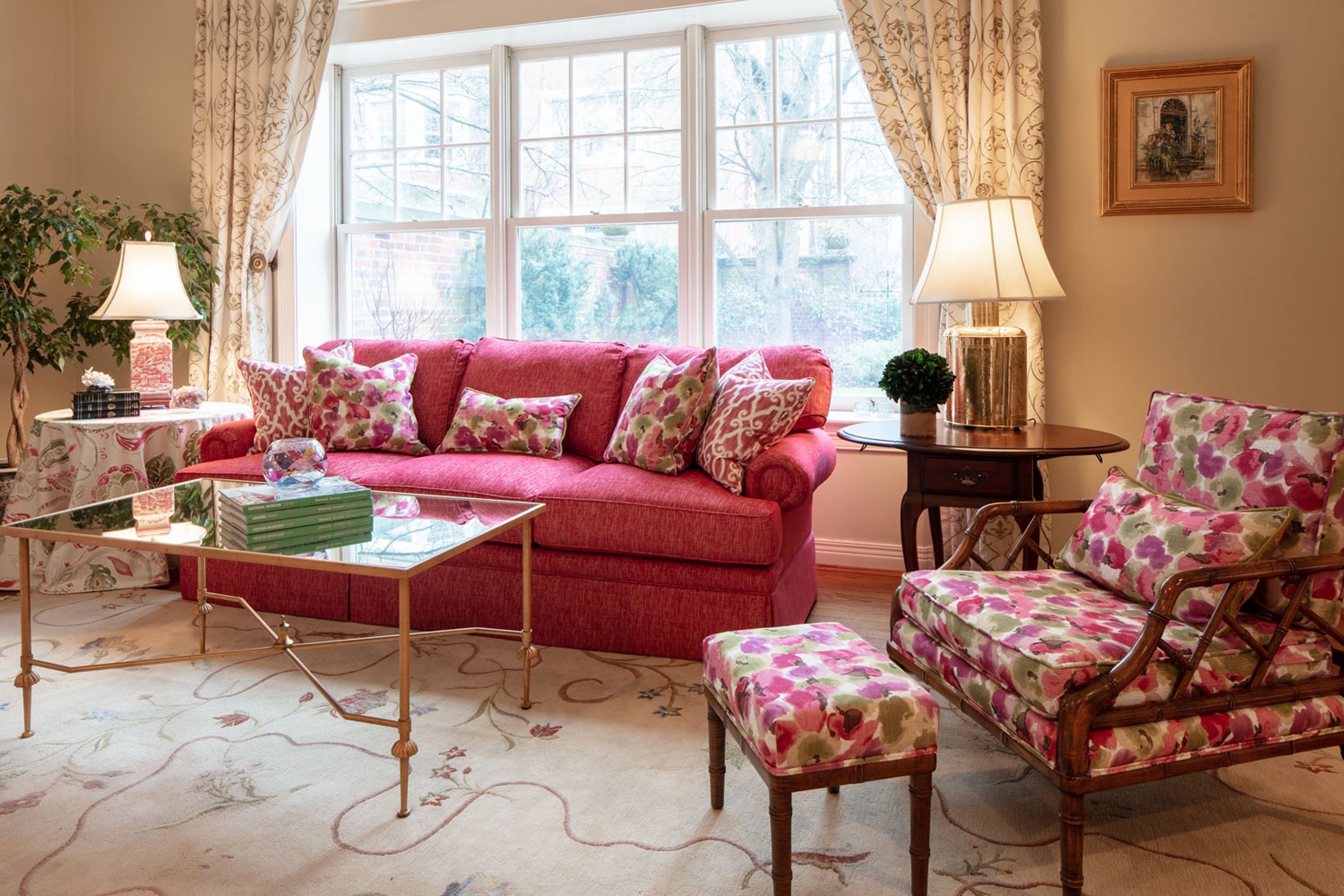 Modern living room with pink sofa, floral chair and center table
