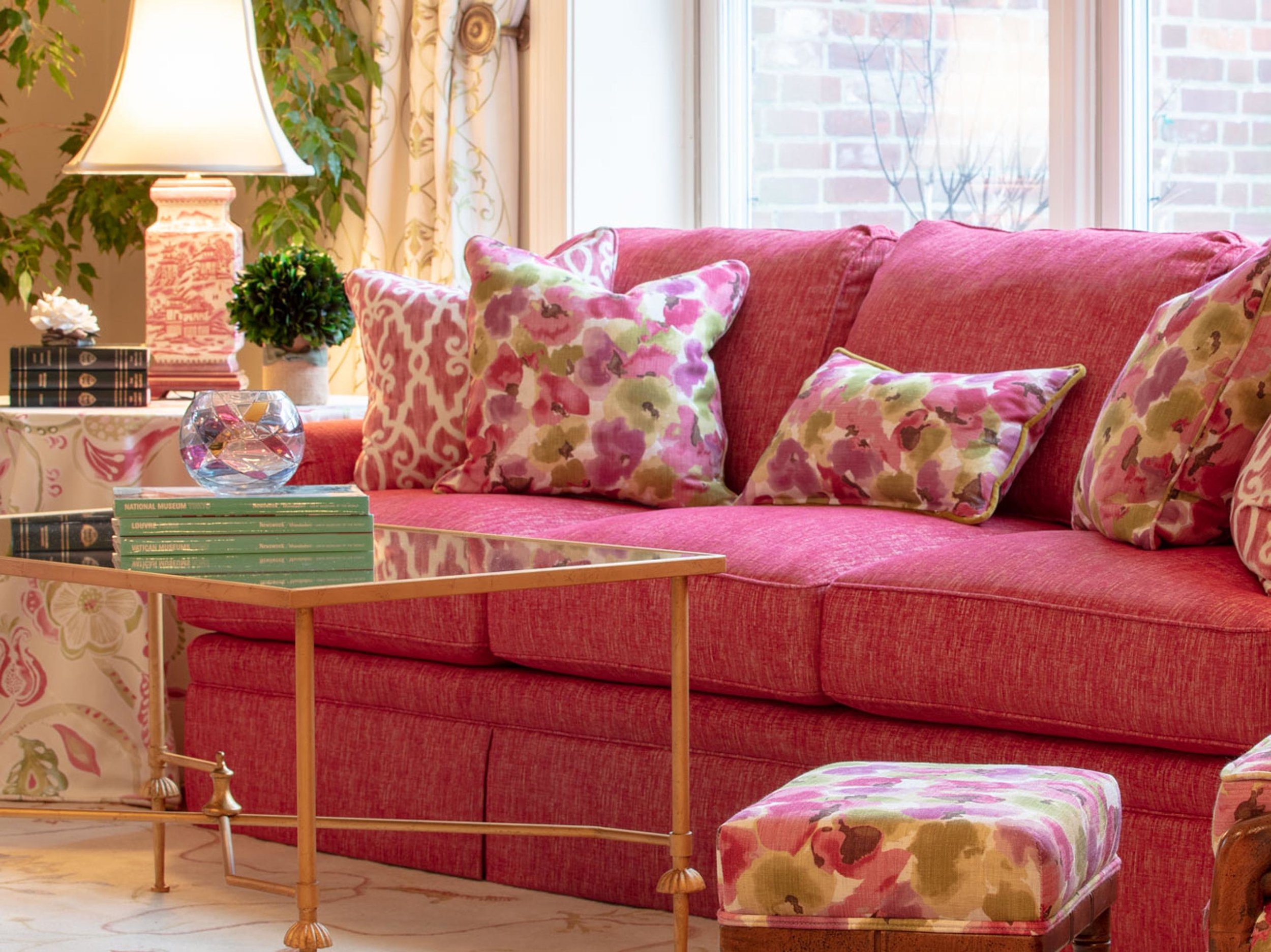 Center table with books on top, and a pink sofa with floral pillows