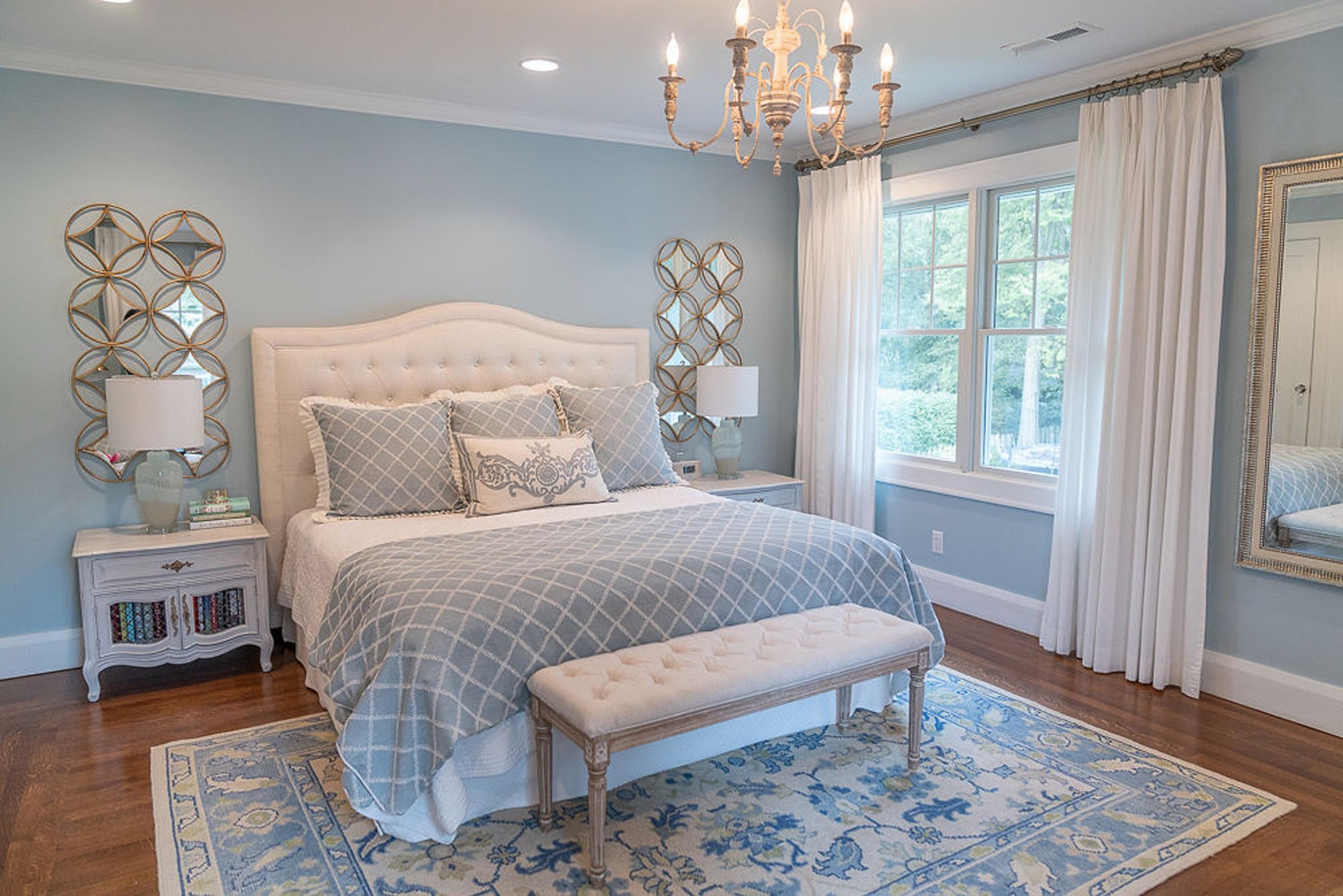 Blue bedroom with large bed, chandelier and table