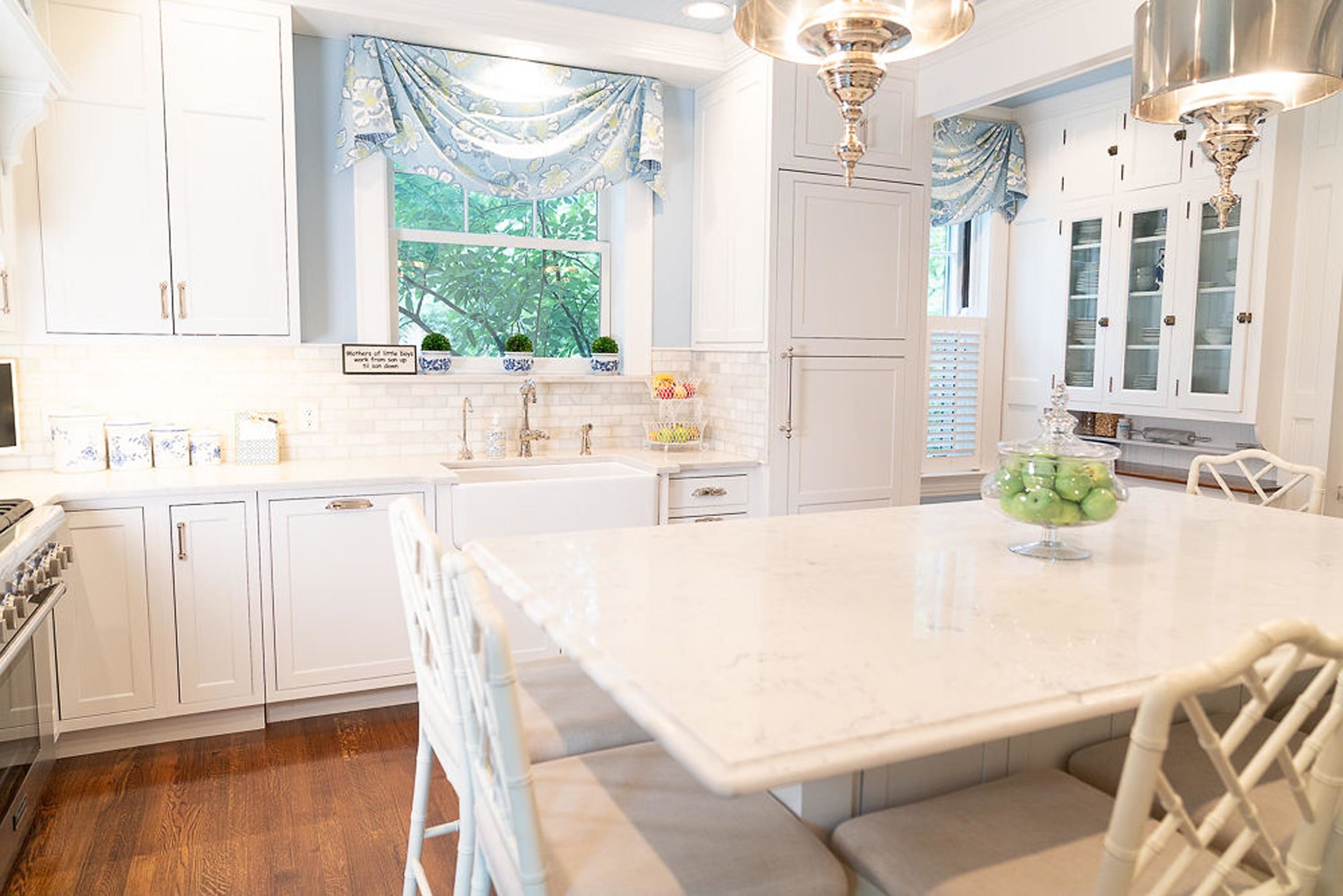 White kitchen room interior with white wooden cabinets and hardwood floor