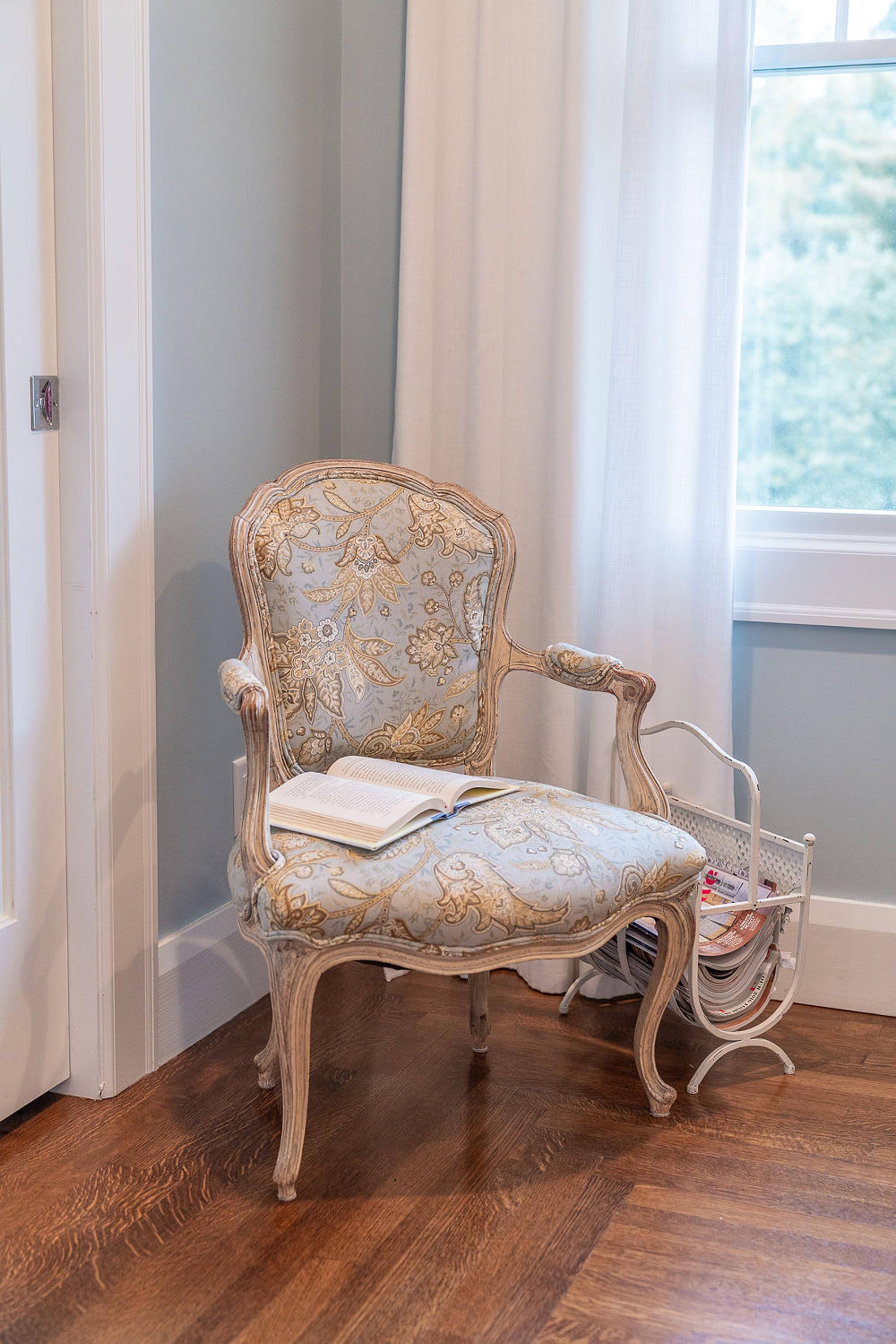 Chair with book, magazine shelves and white curtain
