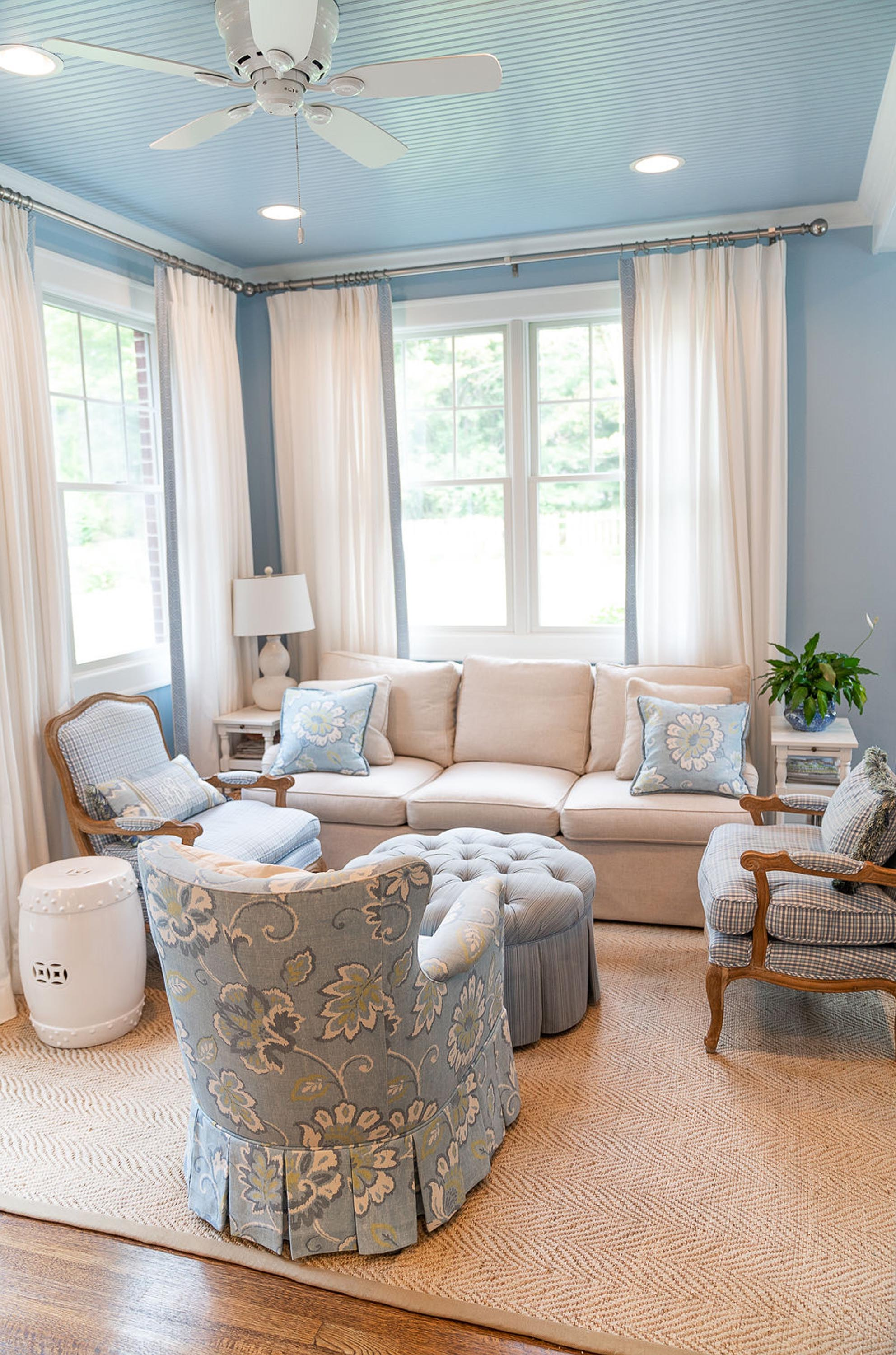 Blue painted living room with sofa, lamp and ceiling fan