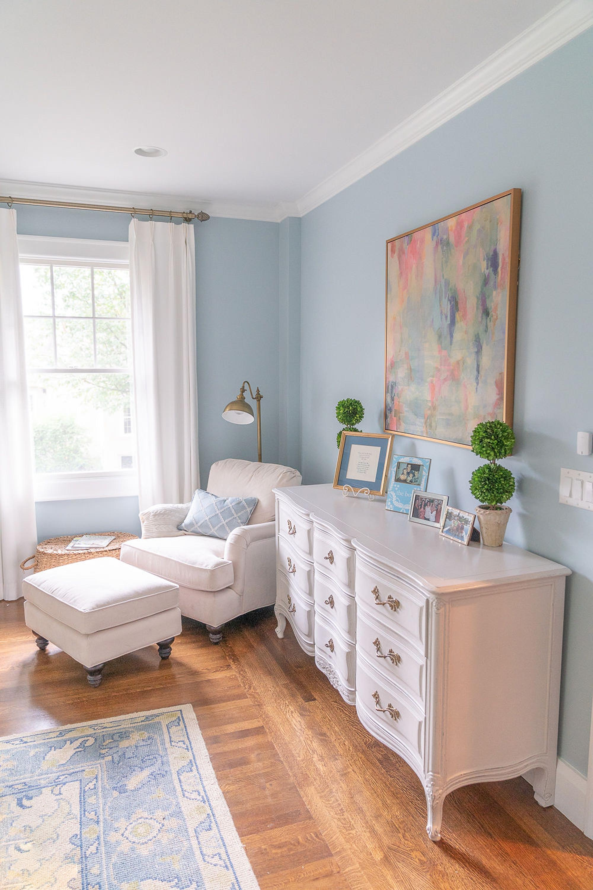 Living room with white chair, white wooden cabinet, frames and artwork on wall